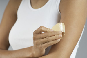 Woman applying patch to arm, mid section